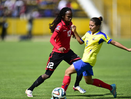 Photo: Trinidad and Tobago winger Ahkeela Mollon (left) flicks the ball around Ecuador left back Angie Ponce during the first leg of the FIFA Women's World Cup Play Off in Quito. (Copyright AFP 2014/Rodrigo Buendia)