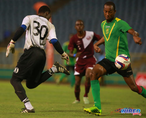 Photo: Mucurapo East Secondary goalkeeper Aaron Enil (left) loses possession to St Benedict's College forward Meriba Des Cartes (right) in the 2014 National Intercol final. (Courtesy Allan V Crane/Wired868)