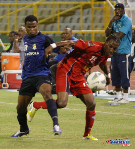 Photo: FC Santa Rosa midfielder Duane Muckette (left) tussles with Caledonia AIA wing back Walter Moore during the 2012 Toyota Cup competition. Muckette and Moore are now based in the United States and Europe respectively. (Courtesy Wired868)