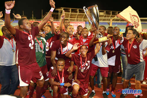 Photo: Goal scorer Tekay Hoyce (far left) and the Mucurapo East Secondary school celebrates with the 2014 Coca Cola National Intercol trophy. (Courtesy Allan V Crane/Wired868)