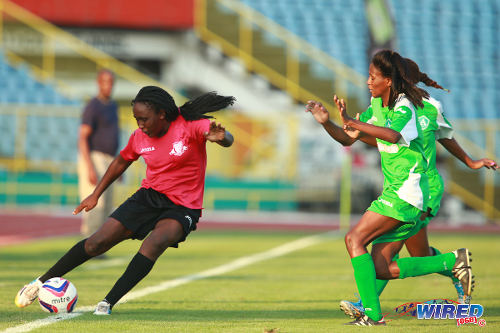Photo: Point Fortin East Secondary student Denicia Prince (left) takes on two St Augustine Secondary defenders in the Coca Cola Girls' National Intercol final. (Courtesy Allan V Crane/Wired868)