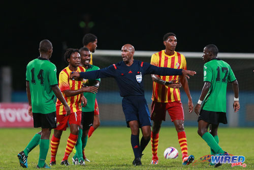 Photo: Referee Neal Brizan (centre) has to separate Point Fortin Civic attacker Andre Toussaint (second from left) from San Juan Jabloteh's Fabian Reid during the 2014 Toyota Classic final. (Courtesy Allan V Crane/Wired868)