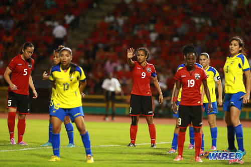 Photo: Trinidad and Tobago captain Maylee Attin-Johnson (centre) signals during yesterday's FIFA Play Off contest against Ecuador in Port of Spain. Looking on are teammates Arin King (left) and Kennya Cordner. (Courtesy Allan V Crane/Wired868)