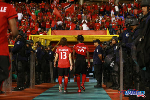 Photo: Trinidad and Tobago players Kennya Cordner (right) and Anique Walker head for the dressing room after their 1-0 FIFA 2015 Women's Cup Play Off second leg defeat to Ecuador on December 2 in Port of Spain. (Courtesy Allan V Crane/Wired868)