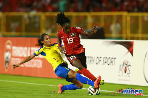 Photo: Trinidad and Tobago attacker Kennya Cordner (right) tries to escape a challenge from Ecuador right back Ingrid Rodriquez during their FIFA Play Off second leg meeting in Port of Spain. (Courtesy Allan V Crane/Wired868)