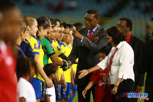 Photo: TTFA president Raymond Tim Kee (centre) gestures to an Ecuador player while Prime Minister Kamla Persad-Bissessar (right) has a word to her grandson before kick off of the FIFA Women's World Cup Play Off second leg on 2 December 2014. (Courtesy Allan V Crane/Wired868)