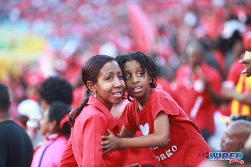 "Photo: An adult and child support the ""Women Soca Warriors"" during their FIFA Play Off second leg clash against Ecuador in Port of Spain on 2 December 2014. (Courtesy Allan V Crane/Wired868)"