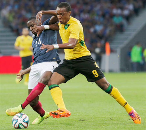 Photo: Eighteen year old Jamaica star Michael Seaton (right) battles for possession with France and PSG midfielder Blaise Matuidi. (Courtesy Jamaica Gleaner)