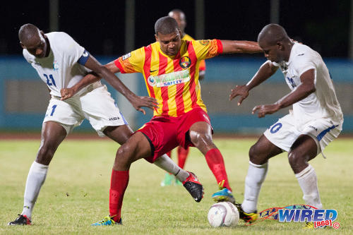 Photo: Point Fortin Civic midfielder Andrei Pacheco (centre) holds off Police FC players Elijah Belgrave (right) and Todd Ryan during a 2013/14 Pro League contest. (Courtesy Allan V Crane/Wired868)