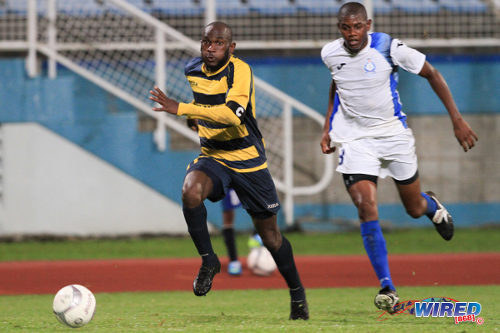 Photo: Club Sando captain Teba McKnight (left) runs at the Police FC defence during the 2013 Toyota Classic competition. (Courtesy Allan V Crane/Wired868)