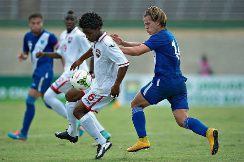 Photo: Trinidad and Tobago National Under-20 midfielder Duane Muckette (left) tries to take the ball under pressure from Guatemala midfielder Andy Ruiz. (Courtesy CONCACAF)