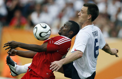 Photo: Trinidad and Tobago's record goal scorer Stern John (left) controls the ball under pressure from England's John Terry at the 2006 World Cup. (Copyright AFP 2015)