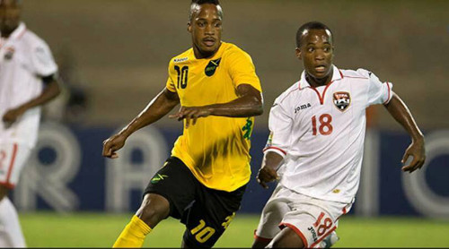 Photo: Trinidad and Tobago midfielder Kevon Goddard (right) tries to keep an eye on Jamaica playmaker Junior Flemmings during CONCACAF Under-20 Championship action in Kingston. (Courtesy CONCACAF)