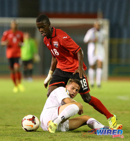 Photo: Trinidad and Tobago National Under-20 midfielder Jabari Mitchell plays the ball around a Curacao player during the 2014 Caribbean Cup. (Courtesy Allan V Crane/Wired868)