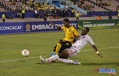 Photo: Trinidad and Tobago defender Jesus Perez (right) tackles Jamaica attacker Cardel Benbow during CONCACAF Under-20 action at Kingston, Jamaica. (Courtesy Yardie Sports/Wired868)