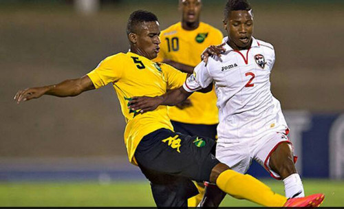 Photo: Trinidad and Tobago captain Shannon Gomez (right) is tackled by Jamaica midfielder Allando Brown during CONCACAF action in Kingston. (Courtesy CONCACAF)