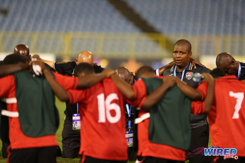 Photo: Trinidad and Tobago National Under-20 coach Derek King (second from right) has a moment with his squad during the 2014 Caribbean Cup. (Courtesy Allan V Crane/Wired868)