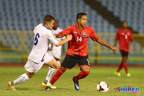 Photo: Trinidad and Tobago midfielder Matthew Woo Ling (right) holds off a Curacao player during the 2014 Under-20 Caribbean Cup. (Courtesy Allan V Crane/Wired868)