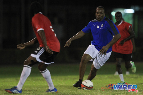 Photo: Trinidad and Tobago's record goal scorer Stern John (right) runs at former 2006 World Cup teammate Brent Sancho during the 2014 Wired Football Festival. (Courtesy Allan V Crane/Wired868)