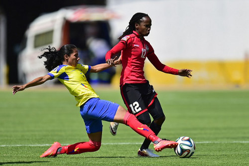 Photo: Trinidad and Tobago national senior team women's star Ahkeela Mollon (right) tries to get past Ecuador player Ingrid Rodriguez during the 2014 FIFA Women's World Cup Play Off. (Copyright Rodrigo Buendia/AFP 2015)