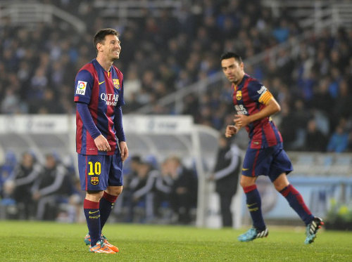 Photo: Barcelona and Argentina star Lionel Messi (left) grimaces during a La Liga match while teammate Xavi looks on. (Copyright Ander Gillenea/AFP 2015)