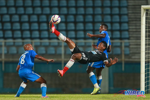 Photo: Central FC striker Willis Plaza (centre) attempts a bicycle kick while Defence Force players Dave Long (right) and Curtis Gonzales look on during Pro League action. (Courtesy Allan V Crane/Wired868)