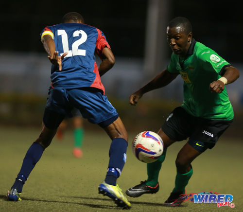Photo: San Juan Jabloteh's Neil Mitchell (right) takes on Caledonia AIA captain Kareem Joseph during Pro League action. (Courtesy Allan V Crane/Wired868)