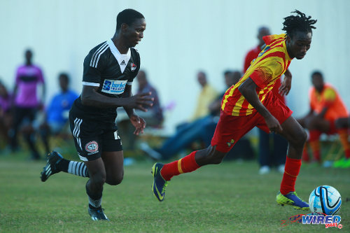 Photo: Point Fortin Civic midfielder Akeem Redhead (right) takes Central FC wing back Kaydion Gabriel for a run. (Courtesy Allan V Crane/Wired868)