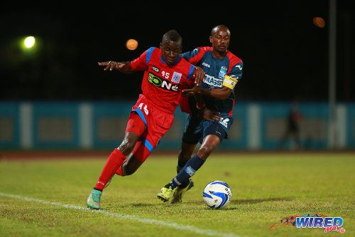 "Photo: St Ann's Rangers attacker Kadeem Corbin (left) takes on Caledonia AIA captain Kareem ""Tiny"" Joseph during a Pro League contest. (Courtesy Allan V Crane/Wired868)"