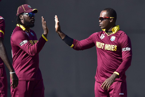 Photo: West Indies veteran Chris Gayle (left) gets a hand from teammate Marlon Samuels during the 2015 ICC Cricket World Cup. (Copyright: AFP 2015/Marty Melville)