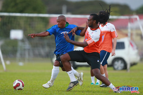 Photo: Rasta versus baldhead! Former W Connection and St Lucia star Earl Jean (left) was more than a match for the younger players like WASA defender Akil Harley. (Courtesy Allan V Crane/Wired868)