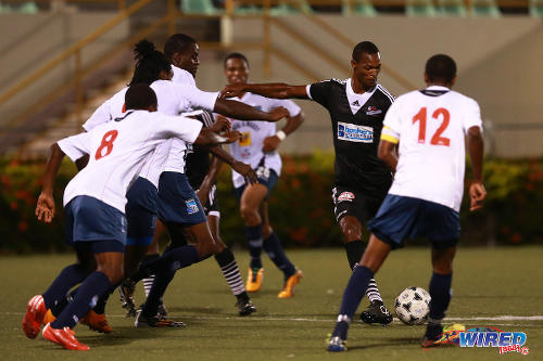 "Photo: Central FC attacking midfielder Ataulla Guerra (second from right) takes on the entire Caledonia AIA defence during a Pro League match. Guerra played under Anthony ""Dada"" Wickham at Trendsetter Hawks. (Courtesy Allan V Crane/Wired868)"