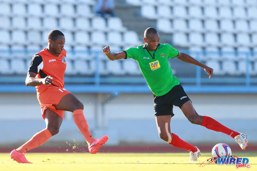 Photo: San Jan Jabloteh striker Brent Sam (right) prepares to drive the ball past Club Sando defender Andre Phillip in the TTFA FA Trophy quarterfinals. (Courtesy Allan V Crane/Wired868)