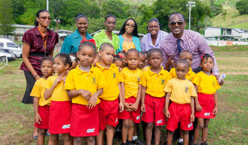 Photo: Sport Minister Brent Sancho (back row, far right) poses with ECCE students. (Courtesy SPORTT)