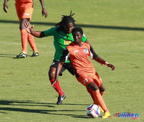 Photo: Club Sando midfielder Akeem Humphrey (right) tries to shake off San Juan Jabloteh player Coneal Thomas during the 2015 TTFA FA Trophy quarterfinal. (Courtesy Allan V Crane/Wired868)