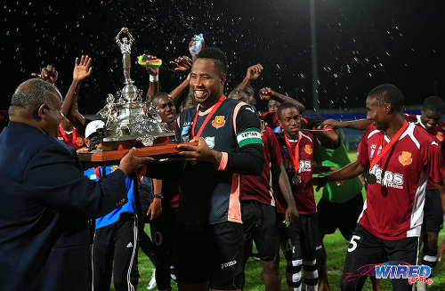 Photo: North East Stars goalkeeper and captain Cleon John (centre) takes the 2015 TTFA FA Trophy from TTFA vice-president Bryan Layne. (Courtesy Allan V Crane/Wired868)