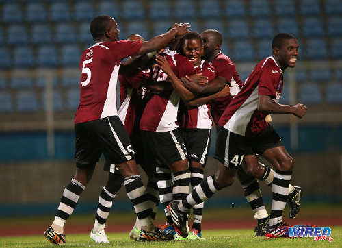 Photo: North East Stars player Keon Joseph (third from right) is congratulated by teammates after scoring the winning penalty against W Connection in the TTFA FA Trophy final. At far right is North East Stars midfielder Neveal Hackshaw. (Courtesy Allan V Crane/Wired868)