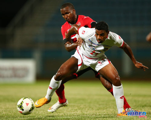 Photo: Trinidad and Tobago captain Khaleem Hyland (background) tries to muscle Panama midfielder Ricardo Buitrago off the ball at the Ato Boldon Stadium, Couva. (Courtesy Allan V Crane/Wired868)