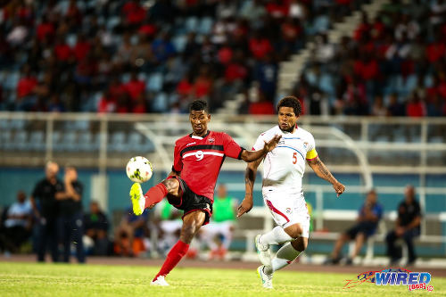 Photo: Trinidad and Tobago forward Willis Plaza (left) tries to keep the ball from Panama captain Roman Torres at the Ato Boldon Stadium, Couva. (Courtesy Allan V Crane/Wired868)