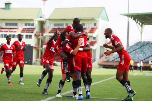 Photo: Central FC players celebrate Sean De Silva's Caribbean Club Championship goal against Alpha United earlier this year. (Courtesy Allan V Crane/Central FC)