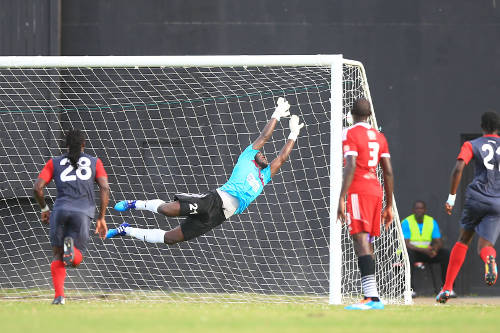 Photo: Central FC goalkeeper Jan-Michael Williams (centre) dives in vain for a Konata Manning free kick during Caribbean Club Championship action in Guyana. (Courtesy Allan V Crane/Central FC)