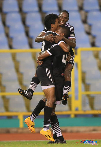 Photo: Central FC players Willis Plaza (left), Kaydion Gabriel (top) and Ataulla Guerra celebrate during their 5-2 win over Point Fortin Civic in the 2014/15 Pro League season. (Courtesy Allan V Crane/Wired868)