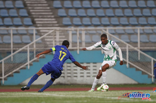 Photo: W Connection playmaker Hashim Arcia (right) dribbles past SAP FC captain Kerry Parker during 2015 Caribbean Club Championship action. (Courtesy Sinead Peters/Wired868)