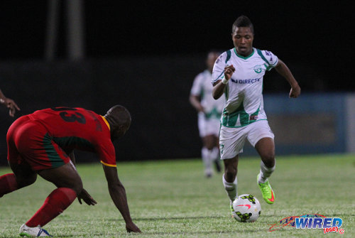Photo: W Connection right back Shannon Gomez (right) runs at a Guyana Defence Force player during 2015 Caribbean Club Championship action. (Courtesy Sinead Peters/Wired868)