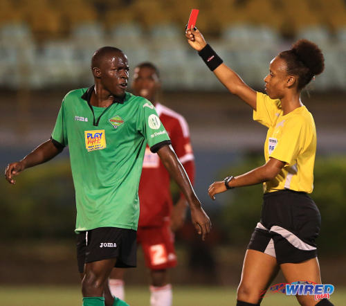 Photo: Referee Crystal Sobers (right) ejects San Juan Jabloteh midfielder Fabian Reid for dissent. (Courtesy Allan V Crane/Wired868)
