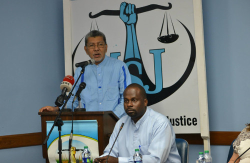 Photo: With the scales of justice in the background, Movement for Social Justice (MSJ) political leader David Abdulah (left) speaks while general secretary Akins Vidale looks on and listens.