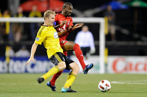 Photo: Former Joe Public star Kerry Baptiste (right) challenges Columbus Crew player Kevin Burns during the CONCACAF Champions League. (Copyright AFP2015/Jamie Sabau)