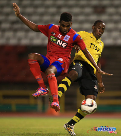Photo: Defence Force striker Devorn Jorsling (right) holds off St Ann's Rangers defender Seon Thomas in Pro League action. (Courtesy Allan V Crane/Wired868)