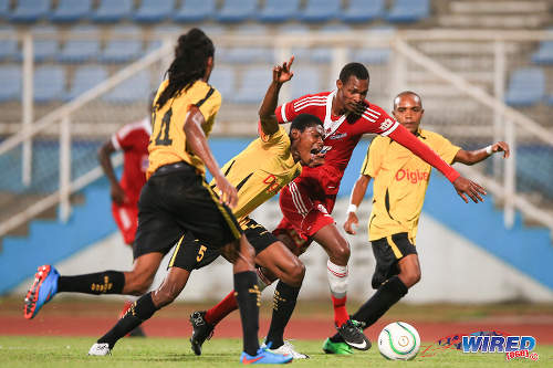 Photo: Central FC midfielder Ataulla Guerra (centre) charges at Don Bosco FC players (from left) Massigno Joseph, Canes Jean Charles and Jean Junior Brenus in a rare offensive burst during the 2015 Caribbean Club Championship semifinal. (Courtesy Allan V Crane/Wired868)