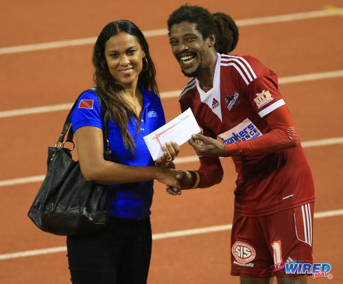 Photo: Central FC Marvin Oliver (right) is presented with a Ruby Tuesday gift certificate as Wired868's 2014/15 Player of the Year by Wired868 director of operations Lou-Ann Sankar. North East Stars midfielder Neveal Hackshaw was also honoured as Wired868's Young Player of the Year. (Courtesy Allan V Crane/Wired868)